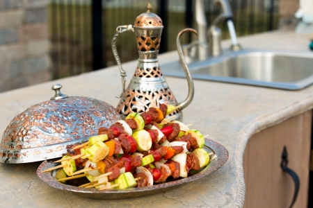 meat counter: Raw meat and vegetable skewers are waiting on the outdoor kitchen counter top. Skewers are in the copper plate  along with complimenting ornamented copper pitcher.