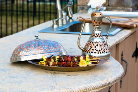 Shish Kebabs on outside kitchen concrete counter top presented in a Arabic style bowl.