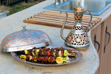 kabob: Sish skewers with vegetables presented in a copper bowl on a concrete counter top kitchen along with a matching copper pitcher.