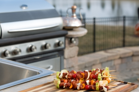 meat counter: Seasoned meat skewers with vegetables on multicolored cutting board, on outside kitchen counter top next to the barbecue.