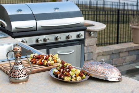Meat skewers with vegetables at the outdoor kitchen on the concrete counter top. Skewers are in the traditional and authentic looking copper plate with complimenting pitcher. Stock Photo
