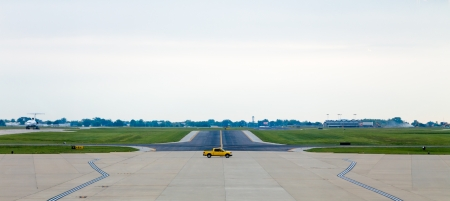 A yellow servicing truck moving on the middle of airport runway photo