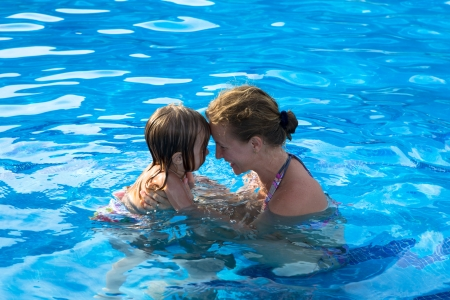 Mother and doughter head to head having passionate great time in the swimming pool.