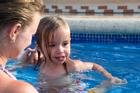 came: Mother and Daughter playful in the pool, daughter came out from the water hair all wet Stock Photo