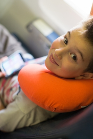 Kid travelling with his player and orange neck pillow on the airplane Stock Photo