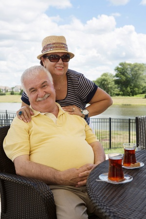 overweight man: Loving senior couple having drinks on an outdoor patio giving the camera beautiful beaming smiles with the woman posing behind her husband with her hands on his shoulders
