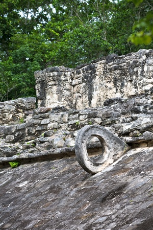 Deadly game, Mayan Ball game at ballcourt, ancient stone goal attached to the pyramid structure. photo