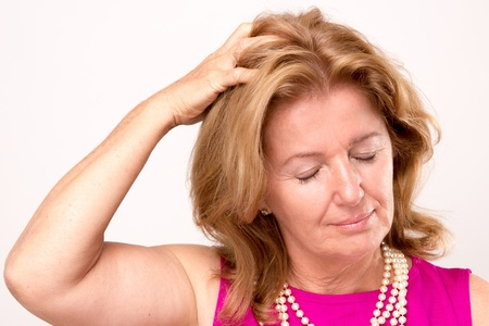 downcast: Attractive middle aged woman with a headache clutching her hand to the top of her head with downcast eyes and a serious pained expression, isolated on white