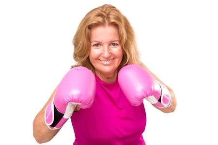 Happy female boxer with her pink gloves guarding herself and getting ready to attack Stock Photo