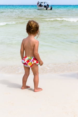 Little girl in her bikini bottom observing the boat on the sea