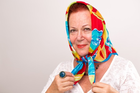 headscarf: Old lady giving a happy satisfied look in her colorful headscarf