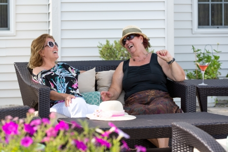 hilarity: Couple women having happy conversations outside at the patio.