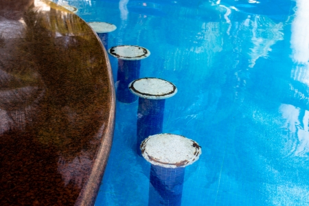 White bar seats in the swimming pool, rusty irons coming out from the seats giving authentic look, horizontal