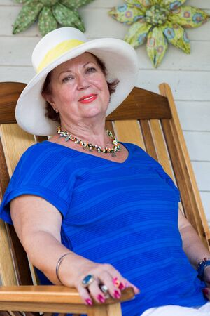 unworried: Older woman with her hat and blue t-shirt looking at camera relaxed and with confidence. She has a look of a sense of comprehending the life. Stock Photo