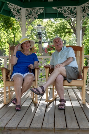 Senior couple resting in the gazebo protecting themselves from the sun photo