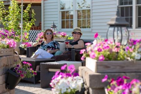 hilarity: Senior ladies having their martinis with cherries in a flower full brick patio. Stock Photo