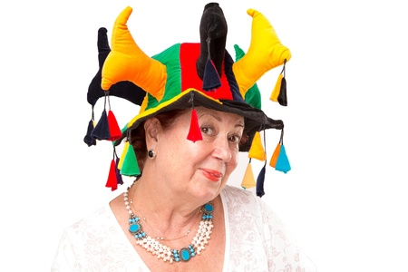 Mischievous senior lady similing to camera happily and mischievously with Jesters hat