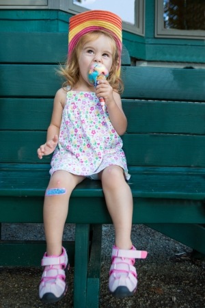 Cute little blond girl in a straw hat sitting on a wooden bench eating a colourful ice cream in the summer sunshine photo