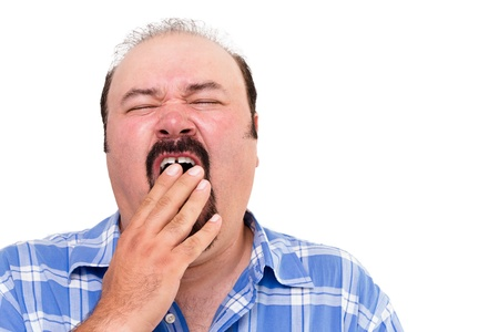 fatigued: Tired man yawning with his hand to his mouth as he tries to fight off his exhaustion, isolated on white