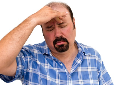 overwrought: man looking worried with hand on forehead isolated on white