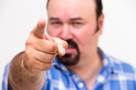 Man pointing an accusatory finger at the camera as he singles out someone to take the blame with selective focus to the hand
