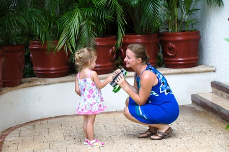 mother and daughter interacting in front of house Stock Photo
