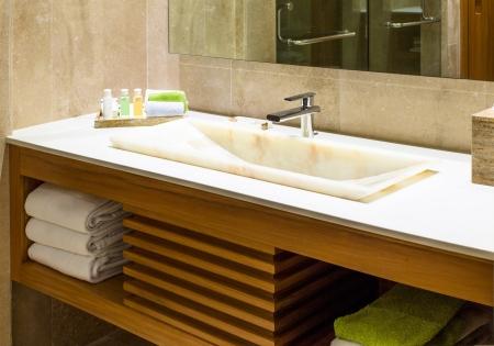 art�culos de perfumer�a: Lavabo de m�rmol moderno en un ba�o o en un hotel cuarto de ba�o con art�culos de tocador y toallas limpias y frescas