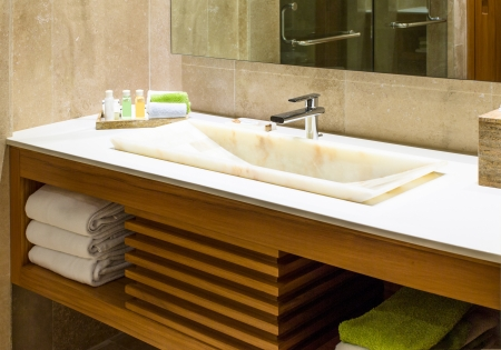 bathroom interior: Modern marble wash hand basin in a restroom or hotel bathroom with toiletries and fresh clean towels