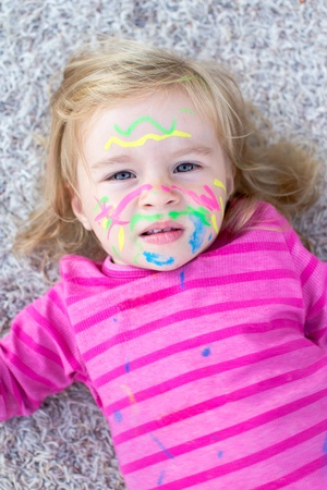 face paint: child with paint on face lying on the floor