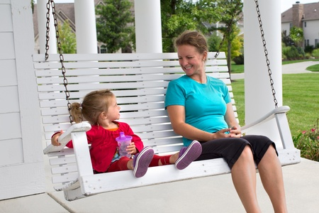 mother and daughter talking and sitting on a swing photo