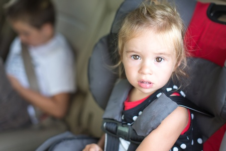 Cute little girl with a serious bewildered expression strapped into a childs safety seat in a vehicle with her young brother visible in the background photo