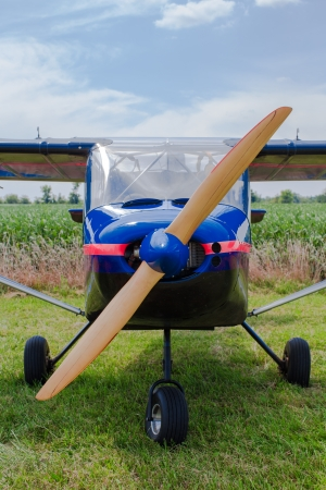 fixed wing aircraft: Propeller and nose of a blue single engine fixed wing aircraft parked in a rural field , closeup view