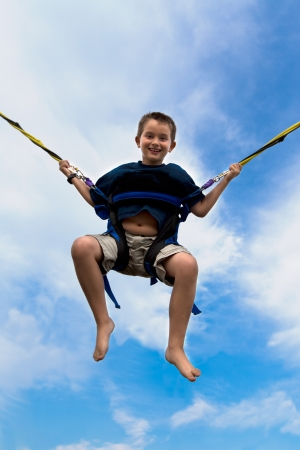 boy barefoot: Young boy swinging high in the air against a cloudy blue summer sky in a harness attached to cables or ropes with a beaming smile of enjoyment