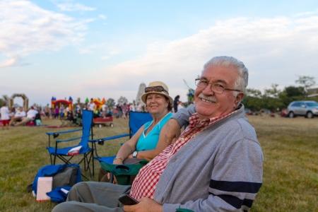 mujeres sentadas: Pareja de ancianos de espectadores sentados en tumbonas en un evento al aire libre en un campo de giro de sonre�r a la c�mara