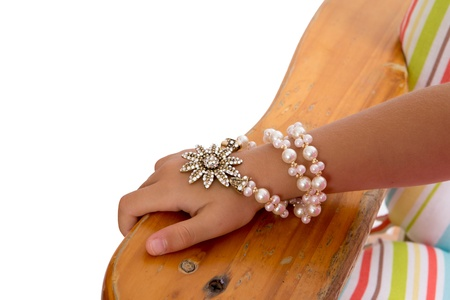 Young girl wearing a pearl and foral bracelet entwined several times around her wrist, close up view of her hand resting on the arm of a wooden chair photo