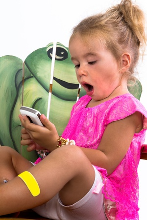 legs open: child playing with smartphone with a frog in the background