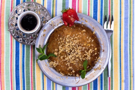 Turkish dessert kunefe on a picnic cloth with mint leaves and sliced strawberry along with Turkish coffee and fork photo