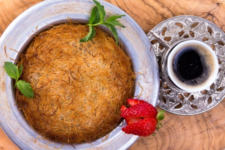 Turkish dessert kunefe isolated on a olive tree table with mints and sliced strawberry along with Turkish coffee photo