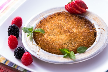 fillo: Turkish dessert kunefe  served in classical aluminum plate on a white plate with mints and sliced strawberry along red and black berries