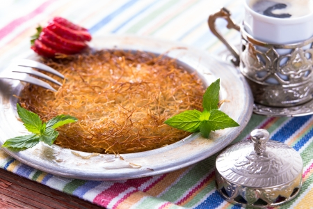 fillo: Turkish dessert kunefe  served in classical aluminum plate on a picnic table with mints and sliced strawberry along with Turkish cofffee Stock Photo