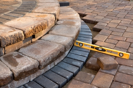 Pavers meets with patio steps and job completion almost done, last check with yellow level Stock Photo