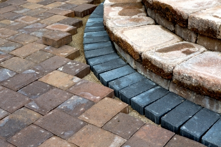 Progress on building brown brick patio steps with contrasting bluish color bricks photo