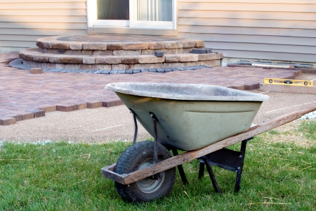 Building Brick Patio With Barrel And Level, Newly Built Steps With Slopes  At Background,