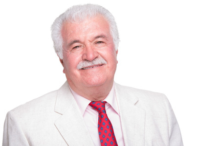 Senior white hair man with a red tie and beige suite smiling satisfied photo