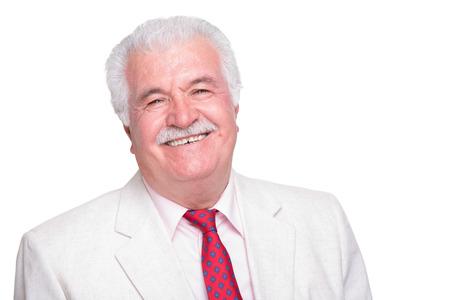 Senior white hair man with a red tie and beige suite smiling trustfully