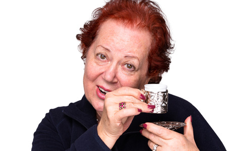 turkish woman: Senior woman welcomingly holding a silver Turkish coffee cup Stock Photo
