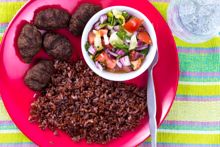 shepperd: Turkish Meat Balls Kofte served with Red Rice Pilaf and Turkish Shepperd Salad on a red plate along with ice water. On table cloth Stock Photo