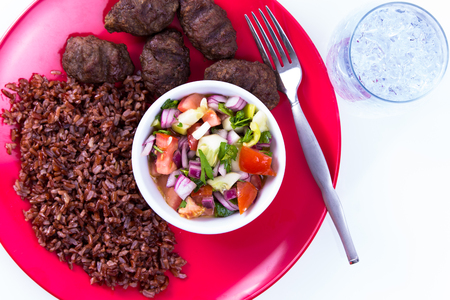 shepperd: Turkish Meat Balls Kofte served with Red Rice Pilaf and Turkish Shepperd Salad on a red plate along with ice water. Isolated on white