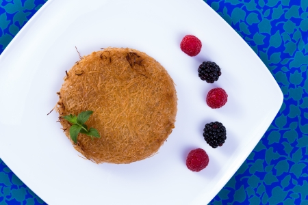 Turkish dessert kunefe on a blue table cloth with mint leaves and berries