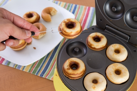 donut shape: Clean hands baking mini donuts in the donut making machine